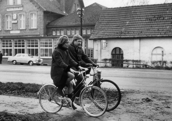 """Auf dem Fahrrad vor dem """"Nobis Krug"""": Johannes Schaaf als """"Spezie"""" – und Hilde Schier als seine Freundin? (Foto: Schamoni-Film)"""